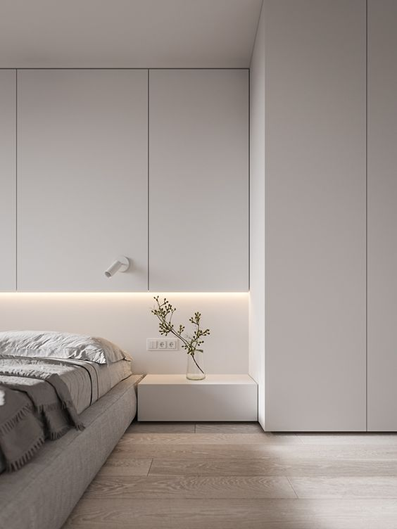 a contemporary meets minimalist bedroom with enough negative space and sleek whiet paneling