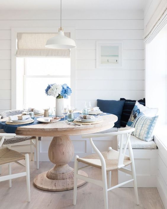 a nautical breakfast nook with wishbone chairs, white shiplap walls and a round vintage dining table