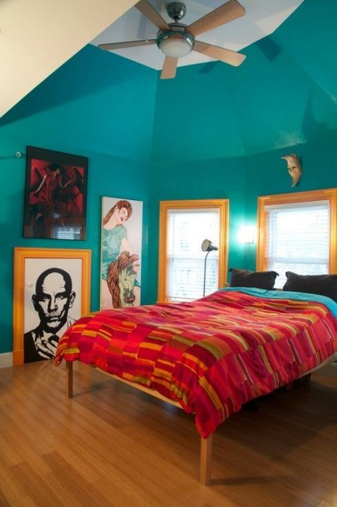 a turquoise bedroom is accented with red bedding and bright yellow framing of the windows