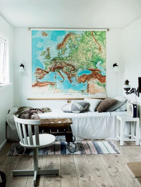 a vintage industrial guest bedroom with a large map as an artwork that inspires travelling