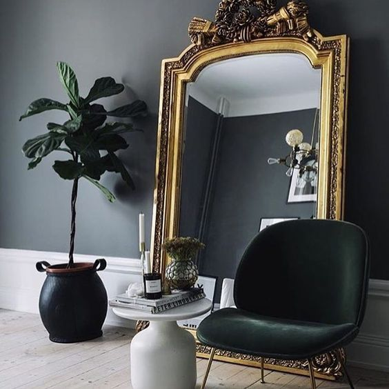 a chic moody nook with an oversized mirror in a gold frame - this mirror takes over the space and makes it wow