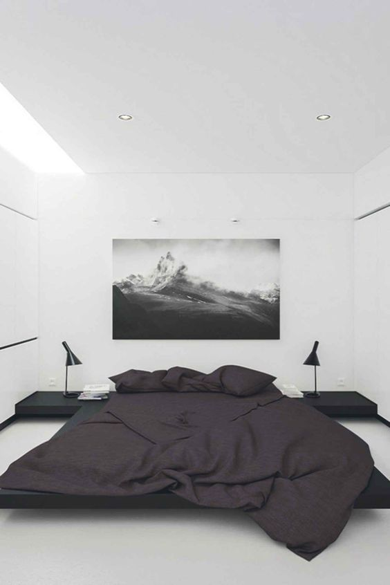 a monochromatic bedroom with a strong contrast and negative space for a relaxed feeling