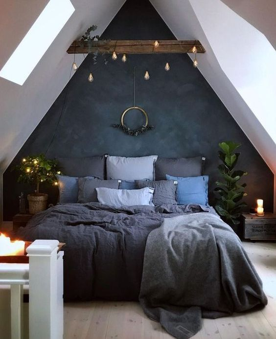 a moody attic bedroom is refreshed with candles and lights hanging over the bed itself