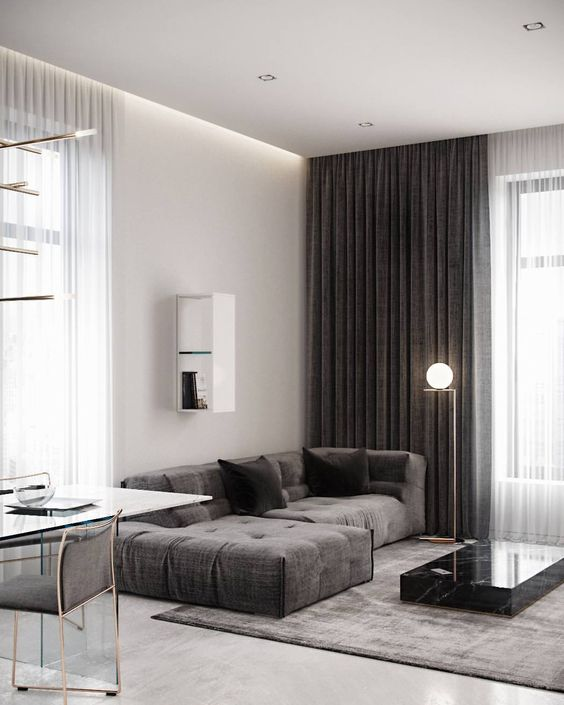 a contemporary home with dark contrastign features - a stone coffee table, dark curtains and upholstery
