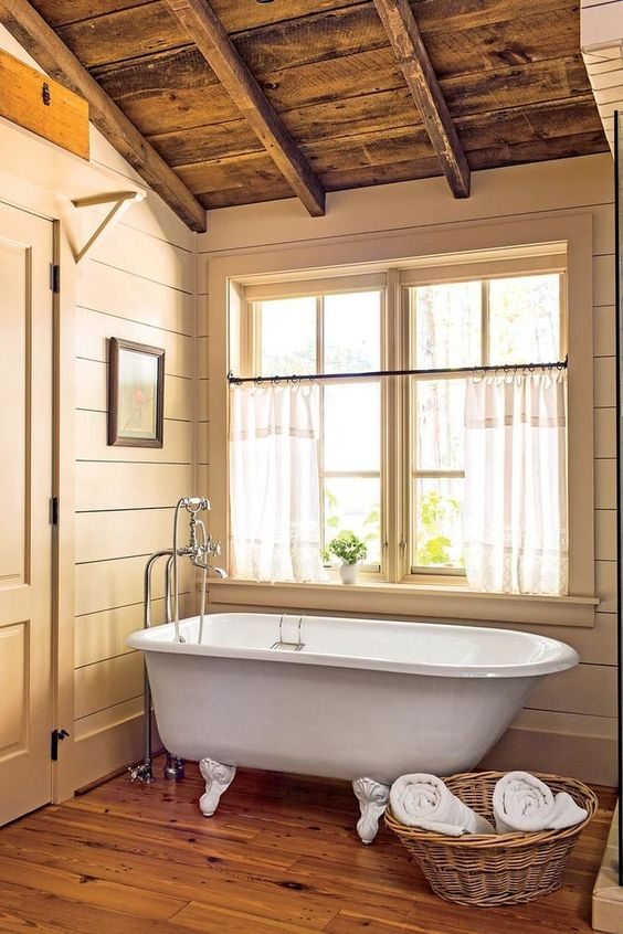 a small farmhouse bathroom in earthy tones, a wooden floor, sandy shiplap on the walls and a basket for towels