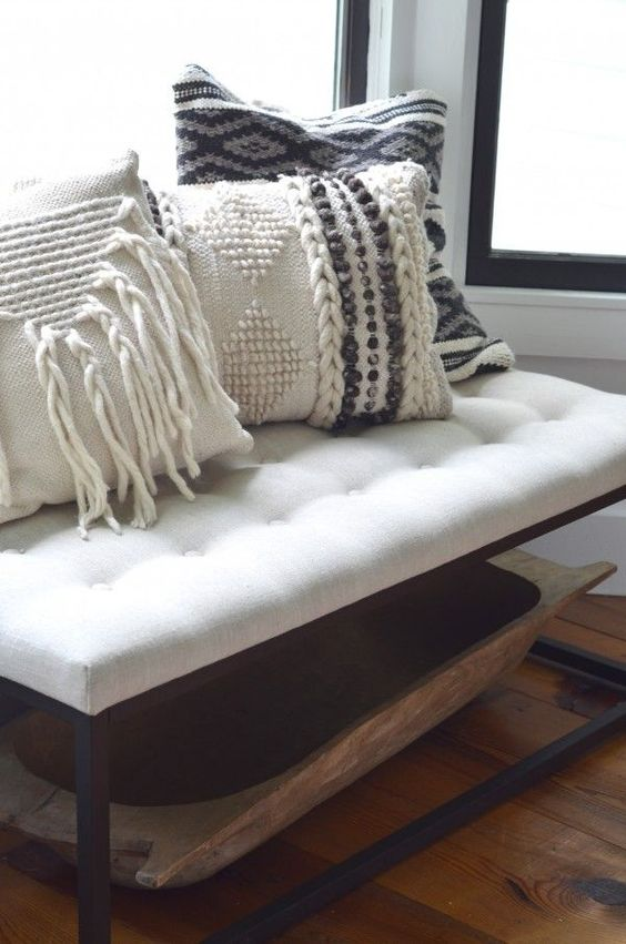 cozy macrame and braided pillows on an entryway bench will make your space very welcoming