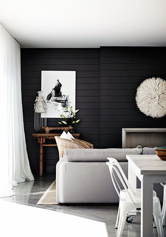 a stylish contemporary living room highlighted with black shiplap on the wall, neutral furniture accents it even more