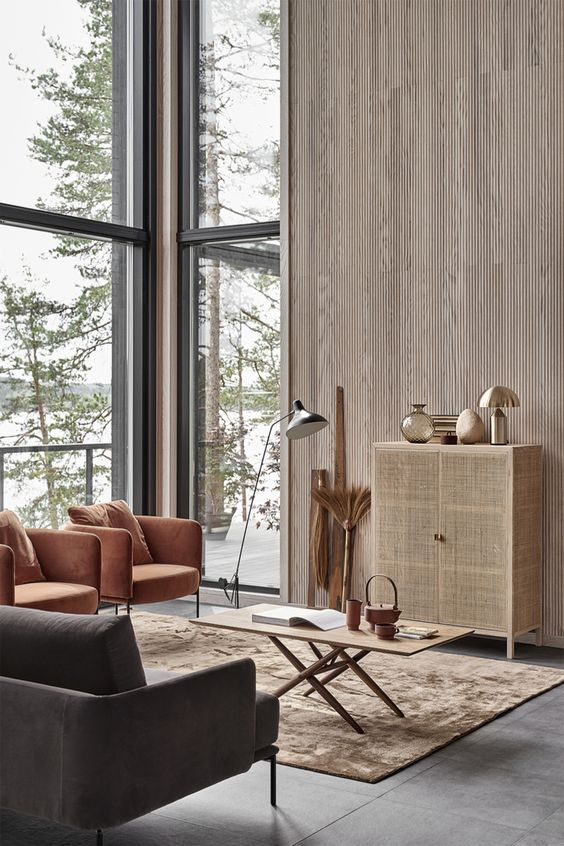 a warm-colored and neutral living room done with wood, cane and leather plus gorgeous views from double height windows