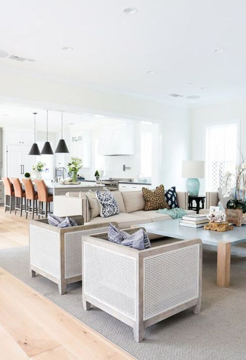some tan cane chairs and a frosted glass and wood coffee table make up a chic modern lounge