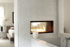 22 a contemporary bedroom and bathroom separated with a wall with a fireplace