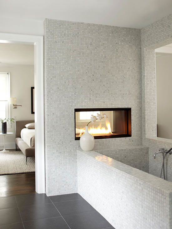 a contemporary bedroom and bathroom separated with a wall with a fireplace
