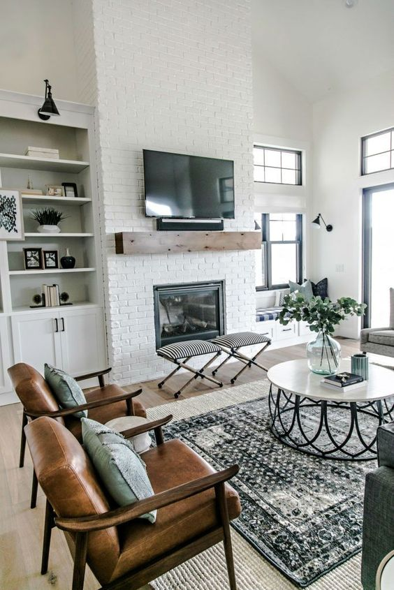 a farmhouse living room with a white brick clad fireplace - bricks accent the fireplace a lot