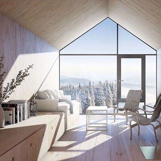 a neutral-colored chalet space with a whole glazed wall that provides the views and fills the space with natural light