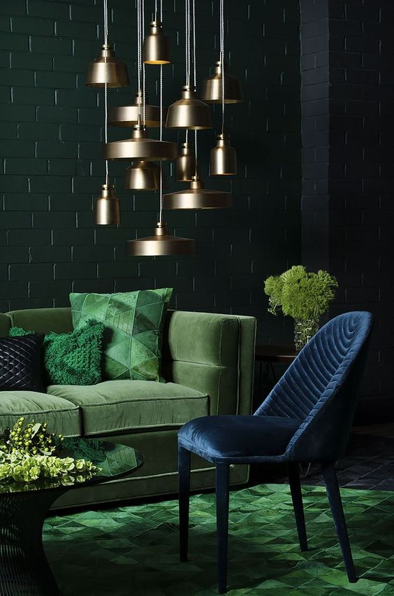 a refined living room with dark green, emerald and navy plus a cluster of brass pendant lamps