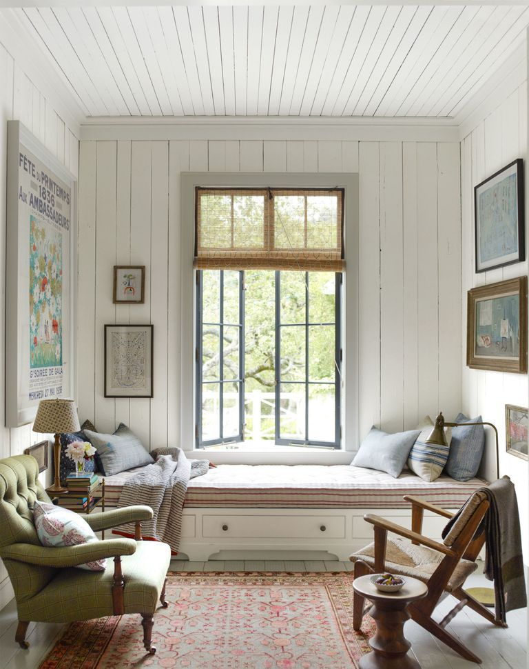 a very welcoming nook done with white shiplap on the walls and ceiling plus comfy vintage furniture