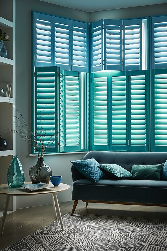 bay windows with blue plantation shutters is a chic and bold idea for a coastal or beach home