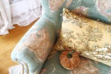 23 a map covered wingback chair with decorative nails detailing, a vintage pillow and a velvet pumpkin is very whimsy