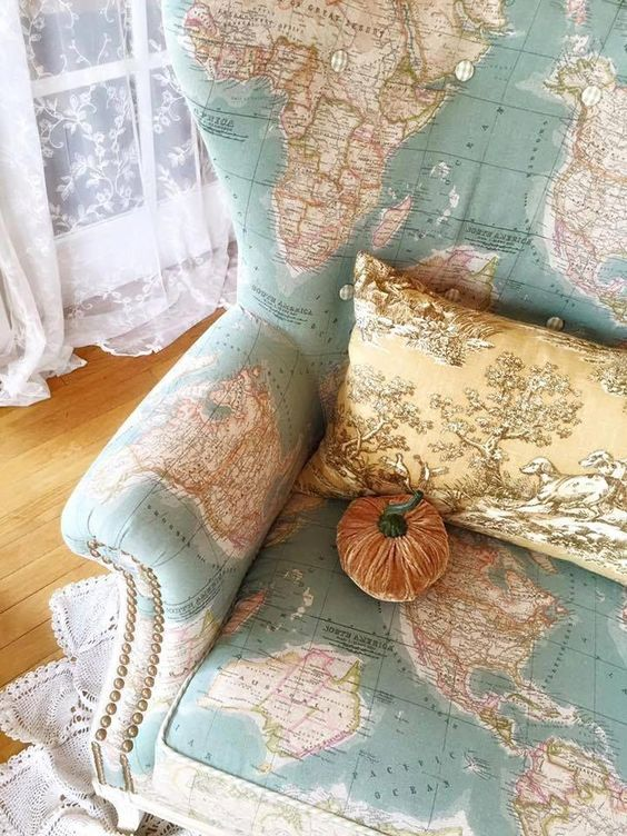 a map covered wingback chair with decorative nails detailing, a vintage pillow and a velvet pumpkin is very whimsy