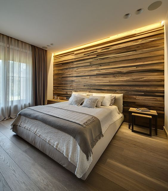 a weathered wood clad statement wall with strip lighting on the top gives you light for reading and accents the bed