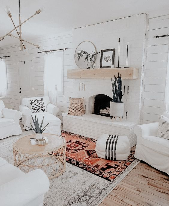 a welcoming white boho living room with white shiplap walls, a white brick fireplace and touches of rattan