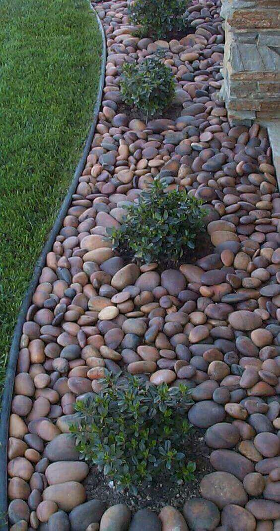 chic and bold pebble garden edging with little greenery bushes growing inside it for a fresher and cooler look