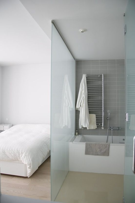 placing a bathtub into the bedroom and separating the zone with glass wall is a cool way to save the space