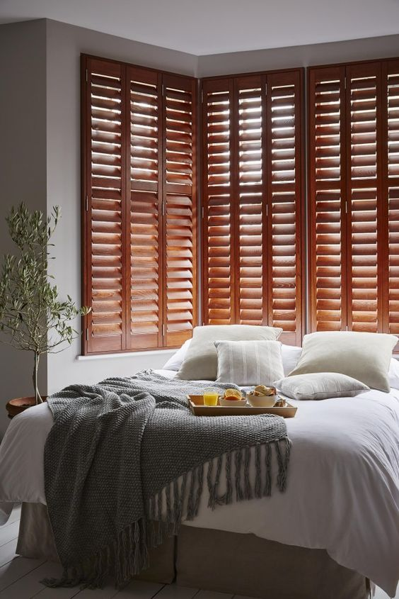 rich-stained shutters in the bedroom is a chic decor idea and a great alternative to a bed headboard