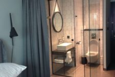 24 a contemporary bedroom with a small en-suite powder room hidden with glass and curtains