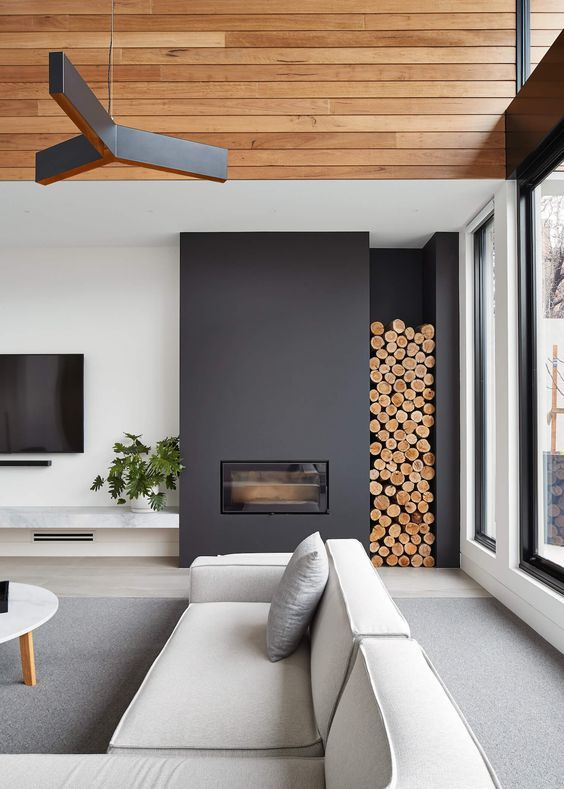 a contemporary living room done with a black sleek fireplace and firewood storage plus a black chandelier