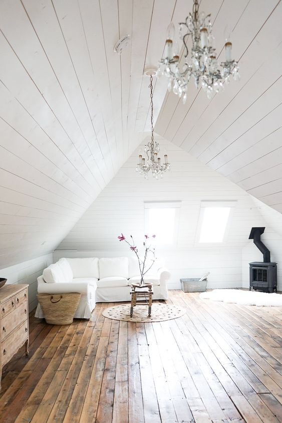 a white attic living room all done with white shiplap around and stained shiplap on the floor looks very cozy and airy