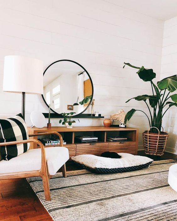 an airy boho chic living room with white shiplap walls, rattan furniture and many potted plants