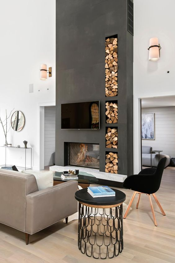 a contemporary living room with contrastign features - a tlall matte black wall with a fireplace and firewood storage plus a black chair