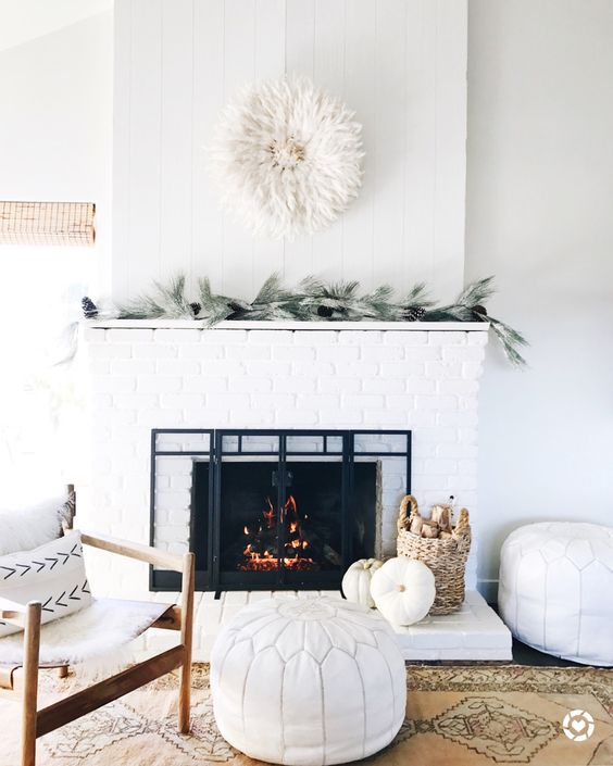 a cozy farmhouse living room done in white, with a white brick clad fireplace to add texture