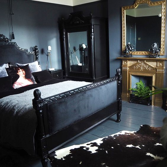 a dark moody bedroom with a couple of mirrors in heavy and carved frames for more light and more chic
