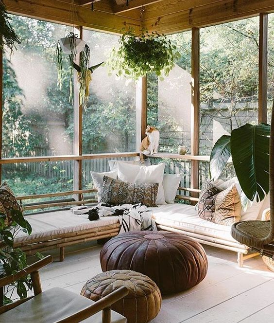 a sunroom with lots of potted greenery plus greenery outside create a cohesive space look