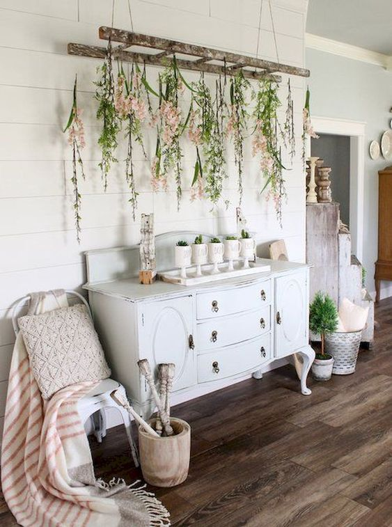 a vintage ladder with greenery and blooms plus potted plants make indoors feel like outdoors