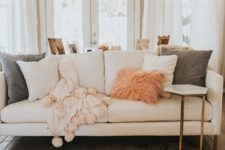 26 creamy, pink and green pillows in various fabrics, a fluffy pink fur pillow and a pink blanket with pompoms for a cozy feel