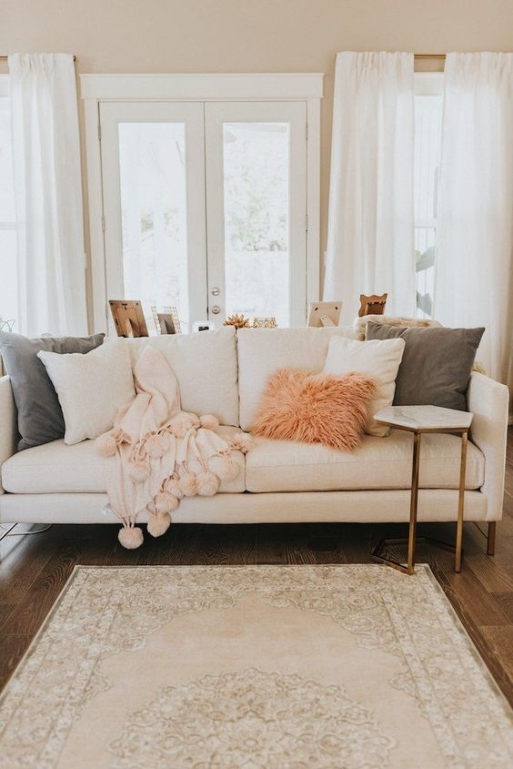 creamy, pink and green pillows in various fabrics, a fluffy pink fur pillow and a pink blanket with pompoms for a cozy feel