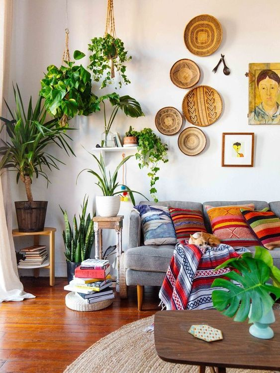 decorative baskets on the wall, many potted plants, colorful printed pillows and a blanket make up a cool boho space
