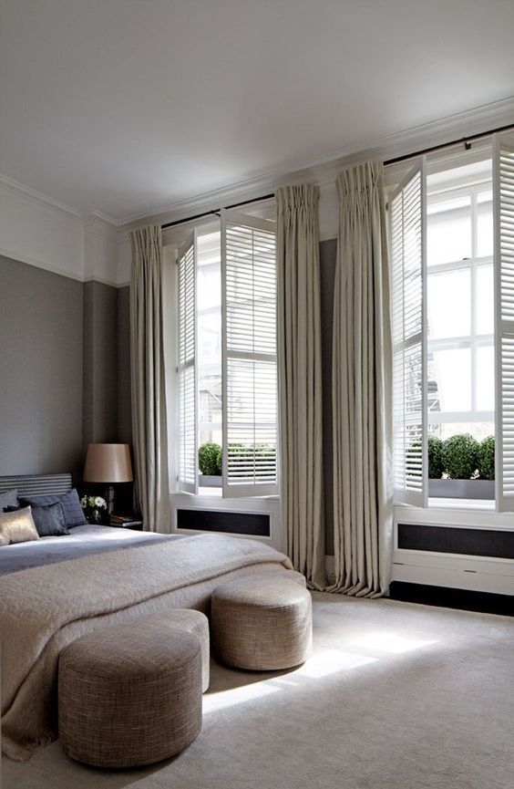 neutral shutters with matching curtains create a sophisticated and welcoming bedroom look adding charm to it