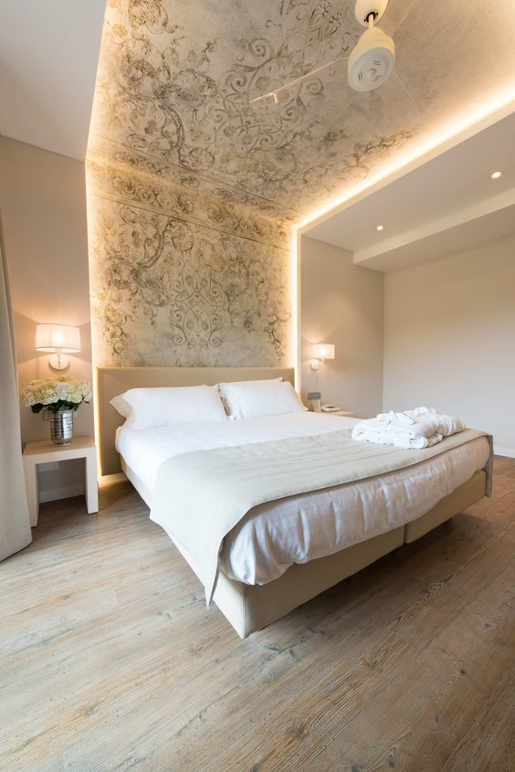 strip lighting integrated into the headboard wall and ceiling highlight the bed and make the space bolder