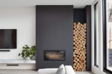27 a minimalist black fireplace with firewood storage by it brings coziness to the space