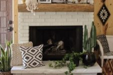 28 a brick clad fireplace with a wooden mantel, potted plants, pillows and artworks for a boho living room