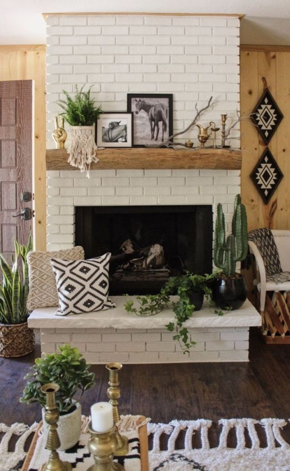 a brick clad fireplace with a wooden mantel, potted plants, pillows and artworks for a boho living room
