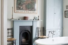 30 a vintage fireplace clad with blue and a mathcing tub and storage piece create a welcoming vintage bathroom