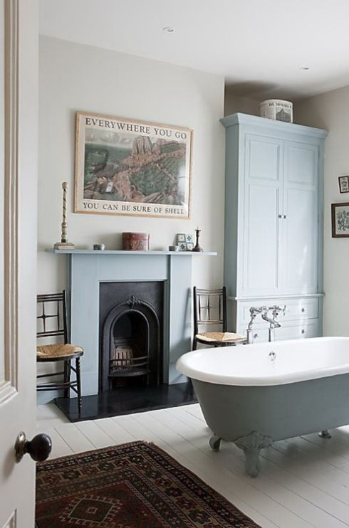 a vintage fireplace clad with blue and a mathcing tub and storage piece create a welcoming vintage bathroom