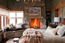 32 a cabin bedroom with a large stone clad fireplace that really warms up the space and makes it wow