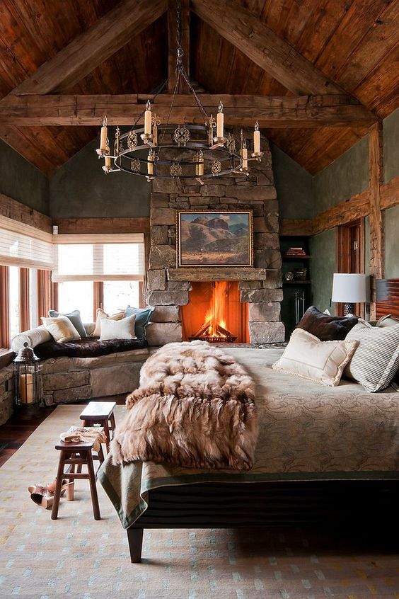a cabin bedroom with a large stone clad fireplace that really warms up the space and makes it wow