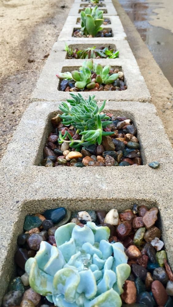 sunken cinder blocks used as planters for succulents and pebbles is a bold modern idea