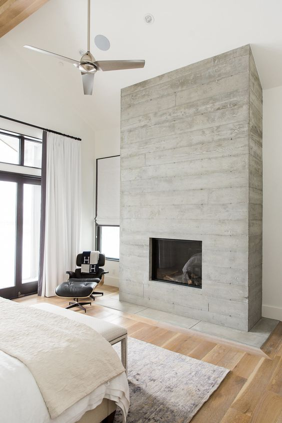 a built in fireplace clad with weathered wood brings an inviting feel to the space and make it cozy